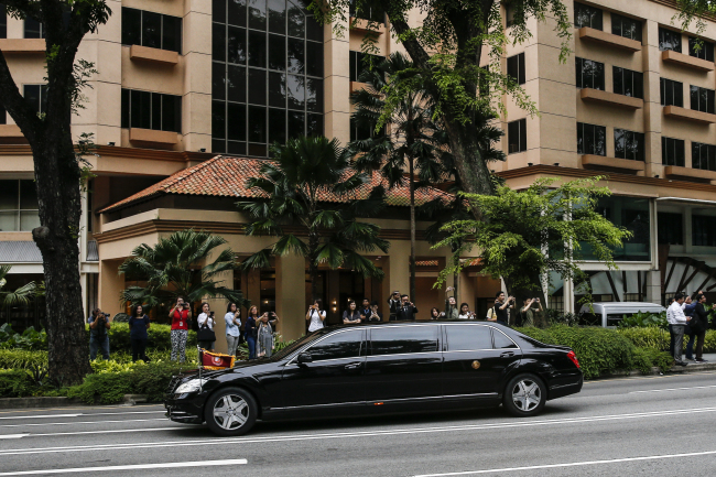 The motorcade of North Korea leader Kim Jong-un leaves the St. Regis Hotel on the way to the Capella Hotel in Singapore, Tuesday, June 12, 2018, where the summit between Kim and US President Donald Trump will take place. (AP-Yonhap)