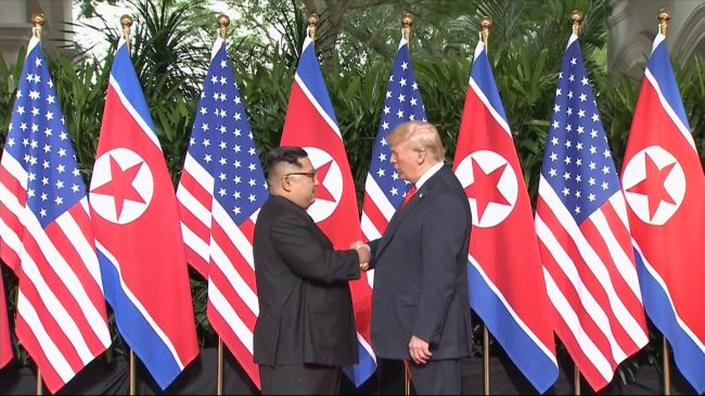 In this image made from video provided by Host Broadcaster Mediacorp Pte Ltd., US President Donald Trump and North Korean leader Kim Jong-un pose together ahead of their meeting at Capella Hotel in Singapore, Tuesday. (AP-Yonhap)