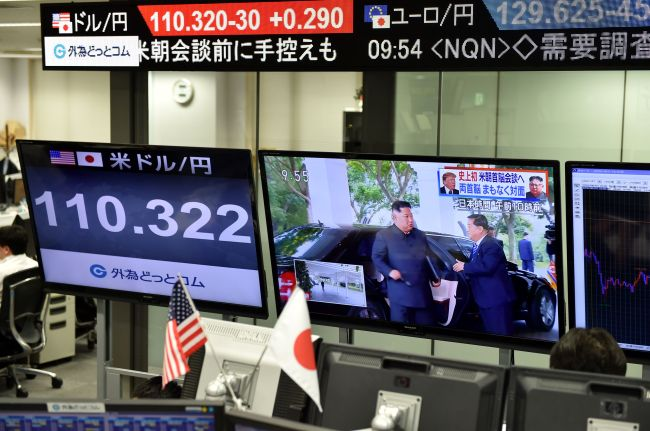 Screens displaying North Korea's leader Kim Jong-un arriving to meet US President Donald Trump in Singapore and the Japanese yen's exchange rate against the US dollar are seen at a foreign exchange trading company in Tokyo on Tuesday. (AFP-Yonhap)