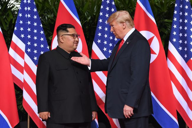 US President Donald Trump (R) gestures as he meets with North Korea's leader Kim Jong Un (L) at the start of their historic US-North Korea summit, at the Capella Hotel on Sentosa island in Singapore on Tuesday. Donald Trump and Kim Jong Un have become on June 12 the first sitting US and North Korean leaders to meet, shake hands and negotiate to end a decades-old nuclear stand-off. (AFP-Yonhap)