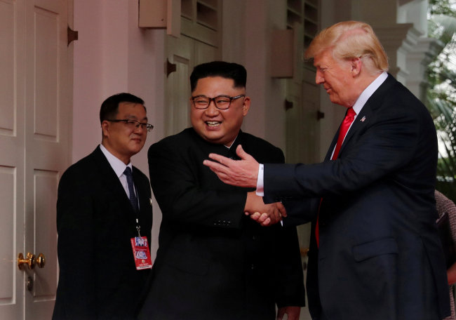 US President Donald Trump shakes hands with North Korea's leader Kim Jong-un at the Capella Hotel on Sentosa island in Singapore June 12, 2018. (REUTERS)