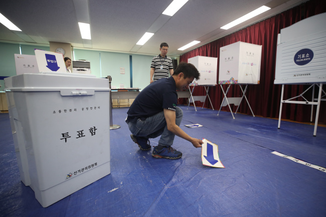 Officials from the Dobong District Office set up one of the polling centers in the northern side of Seoul ahead of the local elections. Yonhap