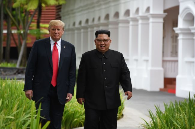 North Korea's leader Kim Jong-un (R) walks with US President Donald Trump (L) during a break in talks at their historic US-North Korea summit, at the Capella Hotel on Sentosa island in Singapore on Tuesday. (AFP)