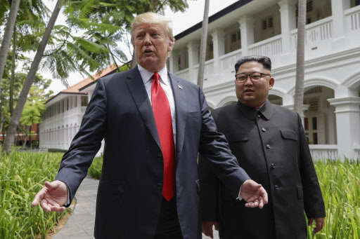 US President Donald Trump and North Korea leader Kim Jong-un stop to talk with the media as they walk from their lunch at the Capella resort on Sentosa Island on Tuesday in Singapore. (AP)