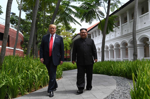 North Korea's leader Kim Jong-un (R) walks with US President Donald Trump (L) during a break in talks at their historic US-North Korea summit, at the Capella Hotel on Sentosa island in Singapore on June 12, 2018. Donald Trump and Kim Jong-un became on June 12 the first sitting US and North Korean leaders to meet, shake hands and negotiate to end a decades-old nuclear stand-off. / AFP PHOTO