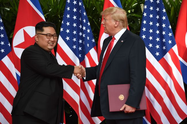 Kim Jong-un shakes hands with Donald Trump after the signing ceremony at the end of their historic US-North Korea summit. (AFP-Yonhap)