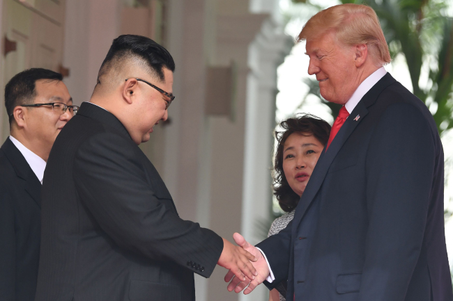 Interpreters Kim Ju-song (far left) and Lee Yun-hyang (second to right) accompany North Korean leader Kim Jong-un and US President Donald Trump, respectively, as the two heads meet at Singapore's Capella Hotel for a summit meeting on Tuesday. (Yonhap)