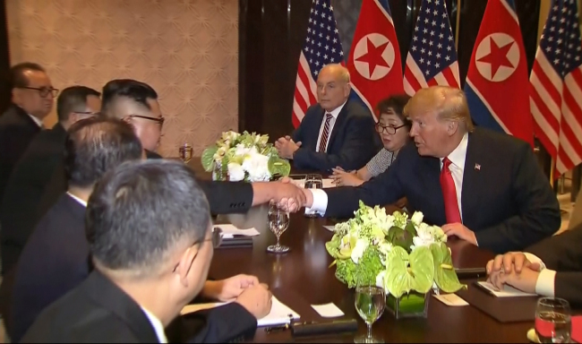Interpreter Lee Yun-hyang (second to right) sits next to US President Donald Trump as he shakes North Korean leader Kim Jong-un's hand over a table during their meeting at Capella Hotel in Singapore, Tuesday. (AP-Yonhap)