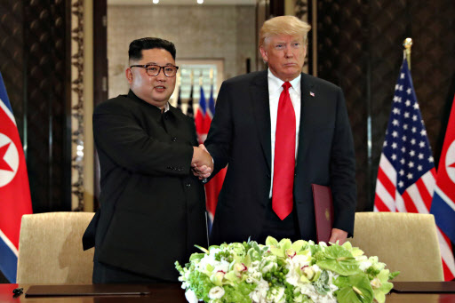 US President Donald Trump shakes hands with North Korea`s leader Kim Jong-un after they signed documents that acknowledged the progress of the talks and pledge to keep momentum going, after their summit at the Capella Hotel on Sentosa island in Singapore June 12, 2018. / REUTERS