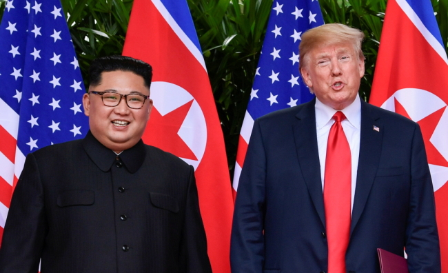 North Korea leader Kim Jong Un and US President Donald Trump stand side by side before their departures after a meeting at the Capella resort, on Sentosa island in Singapore Tuesday. (Reuters-Yonhap)