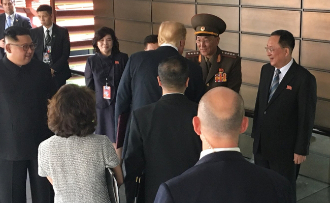 US President Donald Trump, center, shakes hands with North Korean People`s Armed Forces Minister No Kwang-chol at the historic summit between the US and North Korea in Singapore on Tuesday. (Yonhap)