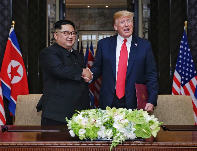 US President Donald Trump (R) and North Korean Chairmain Kim Jong-un (L) shake hands after signing a document during their historic DPRK-US summit, at the Capella Hotel on Sentosa Island, Singapore on Tuesday. (Yonhap)