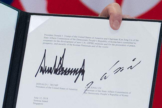 The signatures of US President Donald Trump (L) and North Korea`s leader Kim Jong Un (R) are seen on a document held up by Trump following a signing ceremony during their historic US-North Korea summit, at the Capella Hotel on Sentosa island in Singapore on Tuesday. (AFP-Yonhap)