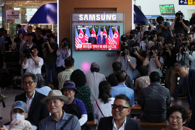 Passers-by gather around a live broadcast of the US-North Summit at Seoul Station in central Seoul on Tuesday. (Yonhap)