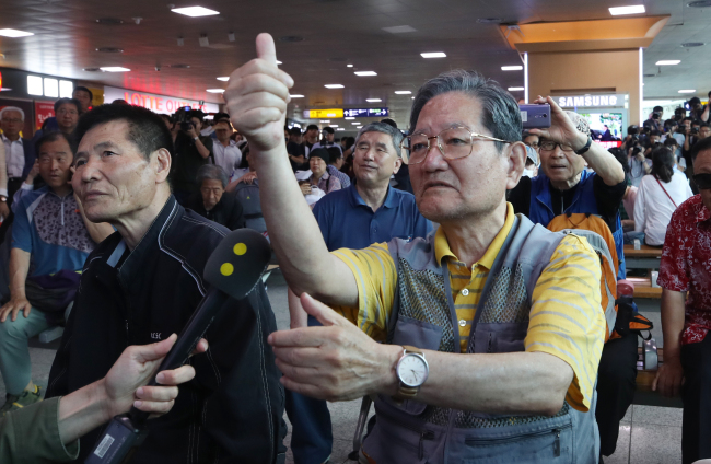 A South Korean man gives a thumbs-up while watching live televised footage of the US-North Summit at Seoul Station in central Seoul on Tuesday. (Yonhap)
