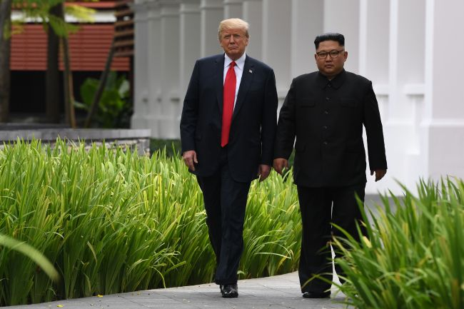 North Korea's leader Kim Jong-un (R) walks with US President Donald Trump (L) during a break in talks at their historic US-North Korea summit, at the Capella Hotel on Sentosa island in Singapore on June 12, 2018. (AFP-Yonhap)