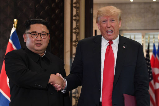 US President Donald Trump (R) and North Korea`s leader Kim Jong-un shake hands following a signing ceremony during their historic US-North Korea summit, at the Capella Hotel on Sentosa island in Singapore on June 12, 2018. Donald Trump and Kim Jong Un became on June 12 the first sitting US and North Korean leaders to meet, shake hands and negotiate to end a decades-old nuclear stand-off. / AFP PHOTO