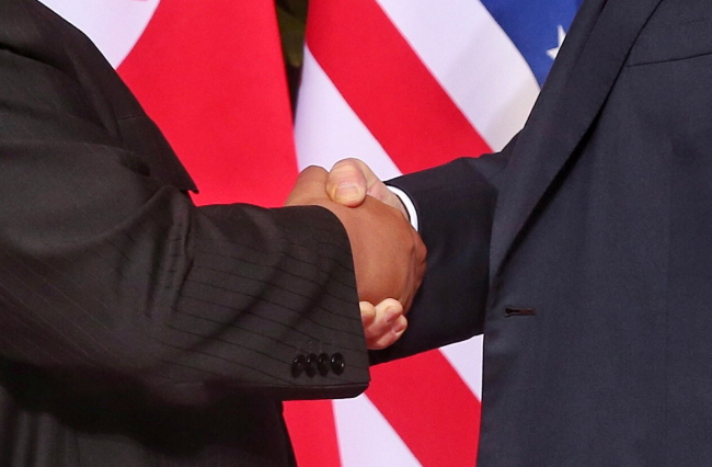 US President Donald Trump (R) and North Korean leader Kim Jong-un (L) shake hands at the start of a historic summit at the Capella Hotel on Sentosa Island, Singapore on Tuesday. (EPA-Yonhap)
