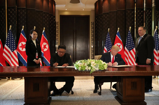 US President Donald Trump and North Korea`s leader Kim Jong-un sign documents that acknowledge the progress of the talks and pledge to keep momentum going, after their summit at the Capella Hotel on Sentosa island in Singapore Tuesday. (Reuters)