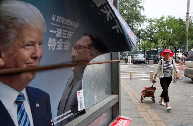 A Chinese woman pulls a trolley bag past a Chinese magazine cover showing US President Donald Trump and North Korean leader Kim Jong Un at a newsstand in Beijing, China on Wednesday. (AP)
