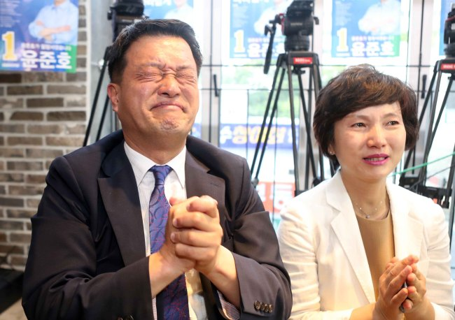 Yoon Jun-ho, candidate of the ruling Democratic Party of Korea running for Busan's Haeundae-B district, on Wednesday rejoices at the exit poll announcement. (Yonhap)