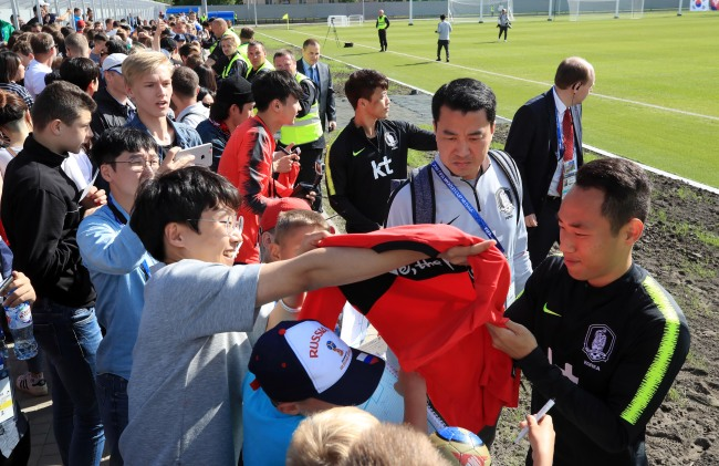 South Korea`s Moon Seon-min (right) sign his autograph for fans after training at Spartak Stadium in Lomonosov, a suburb of Saint Petersburg, on June 13, 2018. (Yonhap)