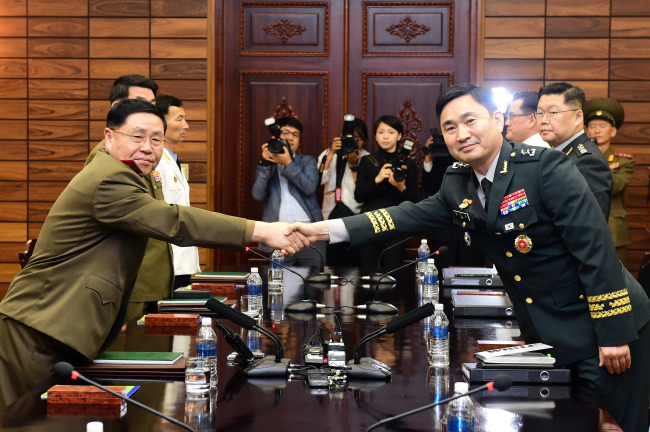 South Korean Maj. Gen. Kim Do-gyun (facing camera) and a North Korean delegate shake hands as a South Korean delegation for high-level inter-Korean military talks crosses over to the North's side of Panmunjeom in the Demilitarized Zone on Thursday. (Yonhap)