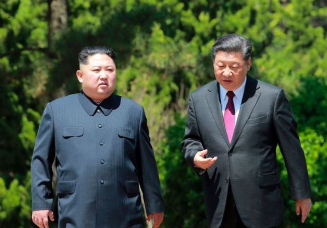 In a file photo taken on May 8, Chinese President Xi Jinping, right, takes a stroll with North Korean leader Kim Jong-un in Dalian in northeastern China. (Yonhap)