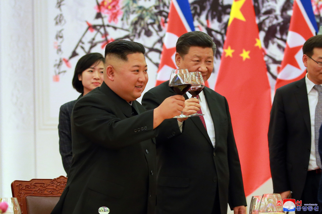 North Korean leader Kim Jong-un and Chinese President Xi Jinping make a toast during an official welcoming dinner in Beijing on Tuesday. (Yonhap)