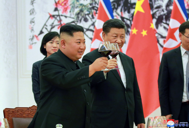 North Korean leader Kim Jong-un and Chinese President Xi Jinping toast at a dinner event held in Beijing on Tuesday. Yonhap