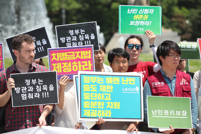 Refugee rights activists hold a rally in front of the presidential office Cheong Wa Dae in Seoul on June 20, 2018. (Yonhap)