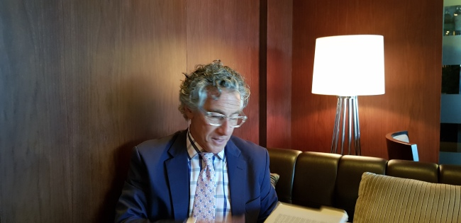 Ira Silverberg looks for information in a book during an interview with The Korea Herald on Wednesday at Coex in Seoul. (Shim Woo-hyun/The Korea Herald)