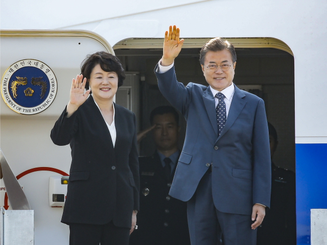President Moon Jae-in and First Lady Kim Jung-sook wave before departing for Russia on Thursday. Yonhap