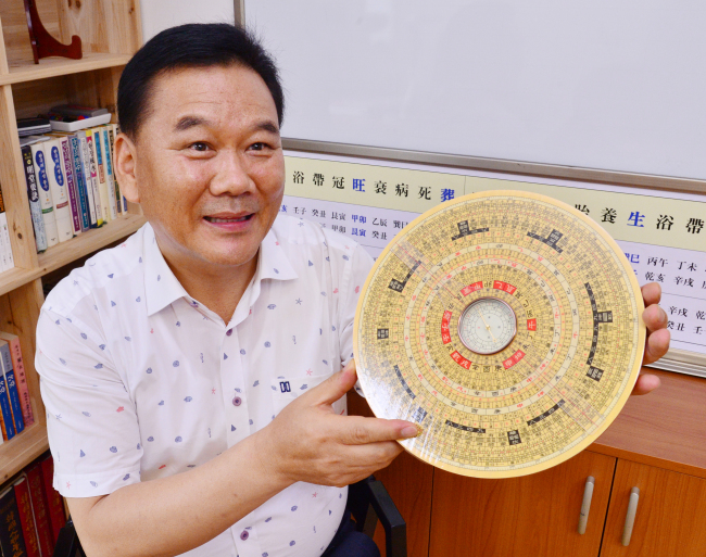 Veteran geomancy consultant Jeon Hang-soo poses with an ancient compass used for divination. (Park Hyun-koo/The Korea Herald)