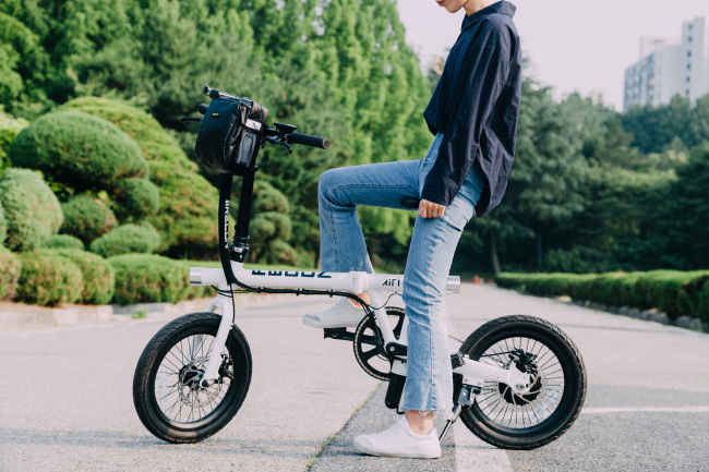 A model sits on Air i, an IoT-based electric bicycle connected to KT's smart mobility platform. (KT)