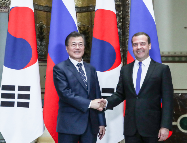 President Moon and Russian Prime Minister Medvedev pose before holding talks in Moscow on Thursday. (Joint Press Corps-Yonhap)