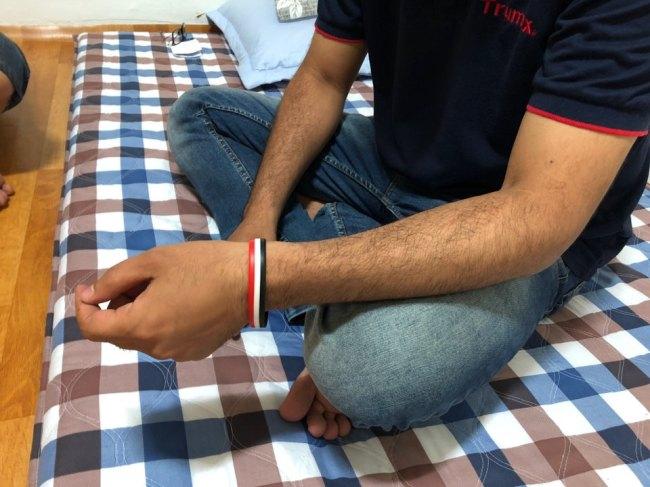 Hane, formerly a journalist in Yemen, wears a rubber bracelet of his country's flag. (Jo He-rim/The Korea Herald)
