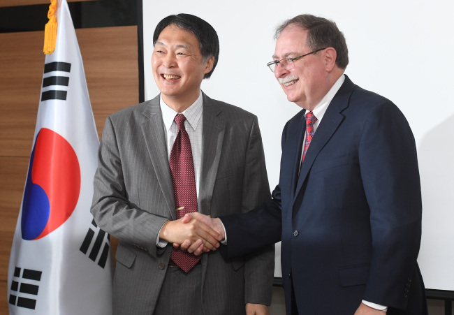 Chang Won-sam (left), the South Korean diplomat in charge of the defense cost sharing negotiations, shakes hands with his US counterpart Timothy Betts before their talks in Seoul on June 26. (Yonhap)