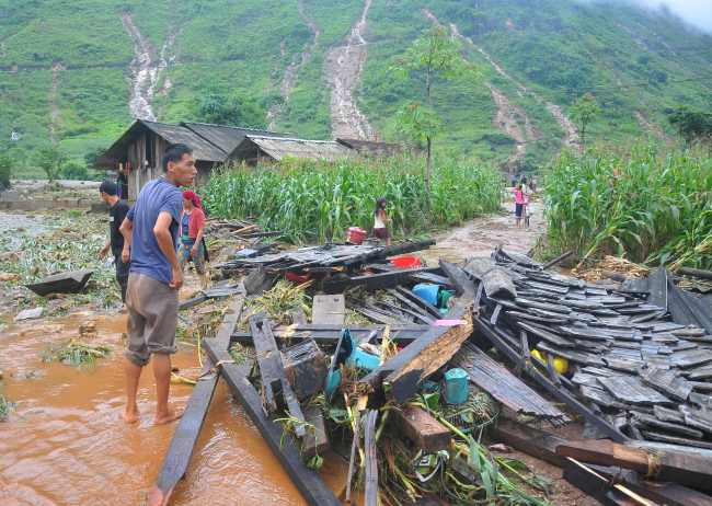 In this picture taken on June 25, 2018 shows a Vietnamese man looking at the debris of his house destroyed by flash floods in northern Ha Giang province. Flash floods and landslides killed 15 people in Vietnam`s mountainous north, officials said on June 26, 2018, after storms ravaged homes and wiped out crops and infrastructure. (AFP-Yonhap)
