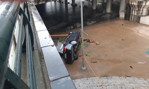 Car falls off Gosanja bridge into Cheonggyecheon on Friday. (Yonhap)