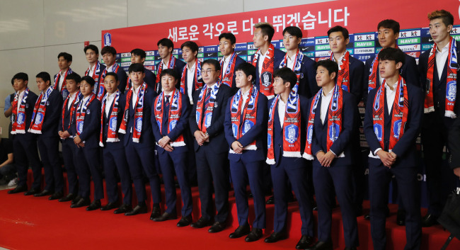 Members of the South Korean men`s national football team pose for pictures in a ceremony at Incheon International Airport after arriving back from the FIFA World Cup in Russia on June 29. (Yonhap)