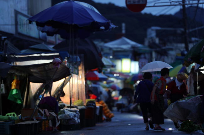 Residents holding umbrellas walk past a closed market in North Jeolla Province on Monday. (Yonhap)