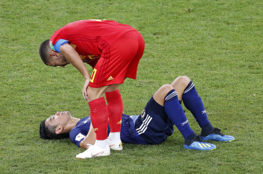 Belgium`s forward Eden Hazard consoles Japan`s midfielder Shinji Kagawa (back) as he lies on the ground at the end of the Russia 2018 World Cup round of 16 football match between Belgium and Japan at the Rostov Arena in Rostov-On-Don on July 2, 2018. / AFP PHOTO