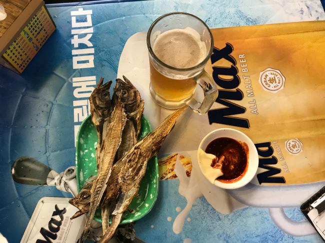 A cold glass of beer is served with nogari and special sauce. A nogari fillet is sold for 1,000 won ($0.90), and a glass of beer goes for 3,500. (Yeo Jun-suk/The Korea Herald)