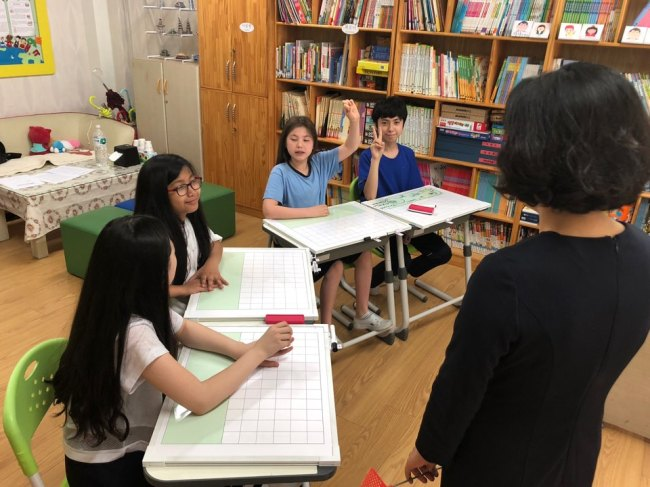 Students with muticultural backgrounds speak with their teacher at a KSL class in Daejeon Sannae Elementary School in Daejeon, on June 28. (Jo He-rim/The Korea Herald)