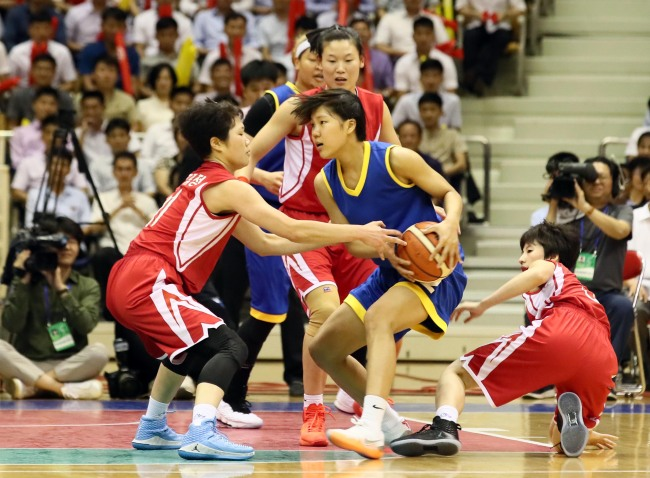 In this Joint Press Corps photo, South Korean player Park Ji-hyun (with ball, in blue) tries to fend off North Korean defenders during a friendly basketball game against North Korea at Ryugyong Chung Ju-yung Gymnasium in Pyongyang on Wednesday. (Yonhap)