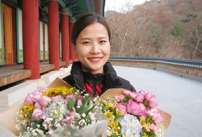 South Korean curler Kim Eun-jung poses for a photo with flowers at Goun Temple in Euiseong, North Gyeongsang Province, on March 12. (Yonhap)