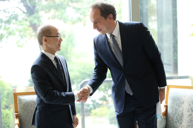 IPCC Chair Lee Hoe-sung (left) shakes hands with French Ambassador to Korea Fabien Penone at the French Embassy in Seoul on Thursday. (Yonhap)