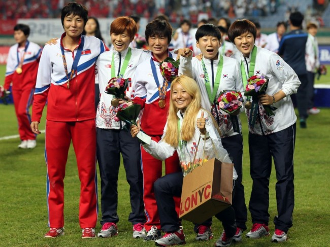 The players from the two Koreas mingled for souvenir photos after the medal ceremony, celebrating the North`s victory over Japan in women`s football during the 2014 Asian Games. (Yonhap)
