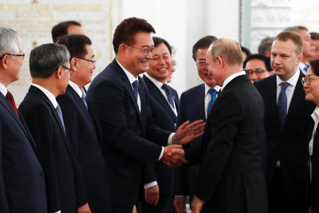 Song Young-gil, Chairman of the Presidential Committee on Northern Economic Cooperation (left) shakes hands with Russian President Vladimir Putin (right) in Moscow on June 22. (Yonhap)